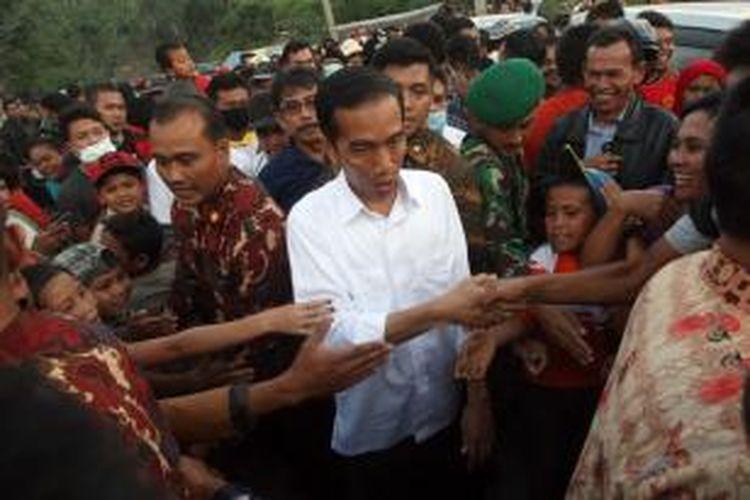 Warga pengungsi erupsi Gunung Sinabung menyalami Presiden Joko Widodo (Jokowi) usai melakukan kunjungan di Desa Gurukinayan, Karo, Rabu (29/10/2014). Blusukan perdana Jokowi ke Tanah Karo tersebut untuk melihat kondisi pengungsi korban erupsi serta memberikan bantuan dan mencari solusi penyelesaian proses relokasi bagi warga korban.