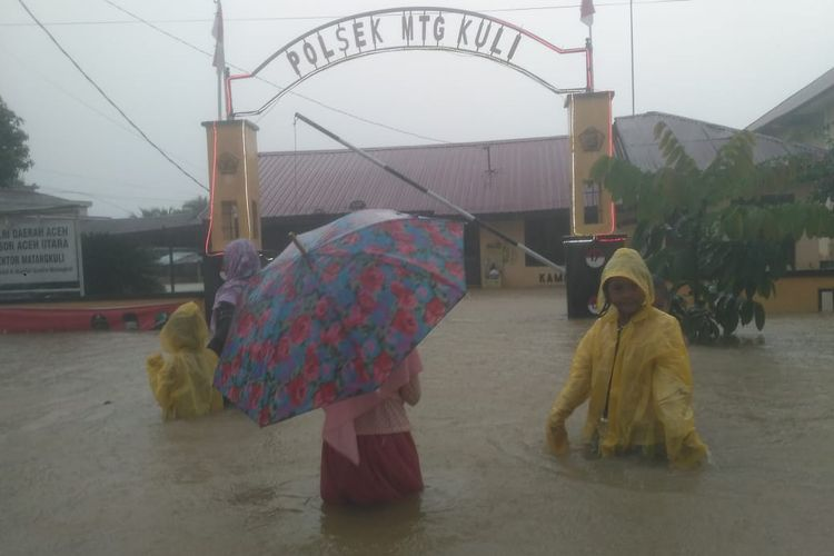 Warga melintas di lokasi banjir depan kantor Polsek Matangkuli, Kecamatan Matangkuli, Aceh Utara, Minggu (6/12/2020)