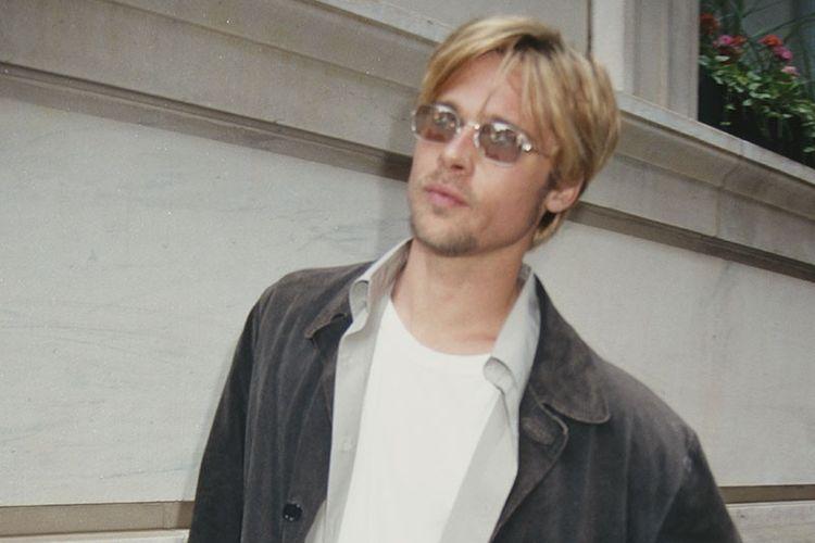 Brad Pitt dengan busana serba putih dengan outer abu-abu muda dan pekat
