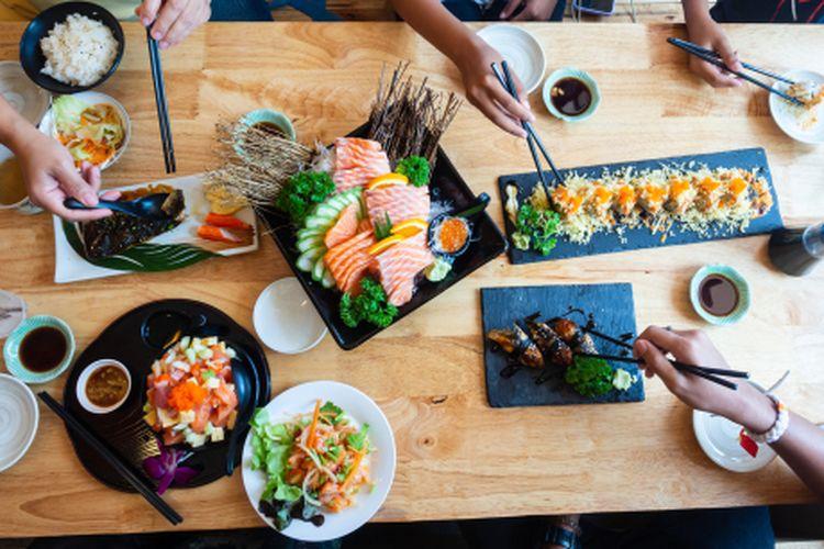 Satu set sushi di atas meja kayu di restoran Jepang, irisan salmon segar untuk menu sushi. Pesta teman atau keluarga makan sushi menggunakan batang bambu