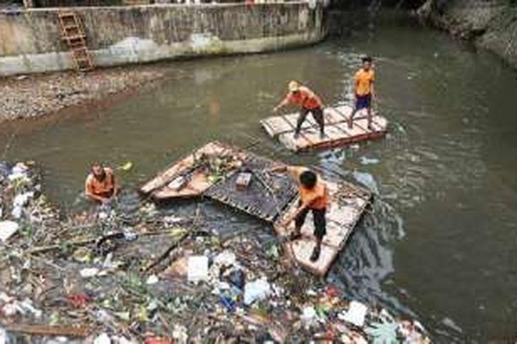 Petugas Unit Pengelola Kebersihan Badan Air, Taman, dan Jalur Hijau Dinas Kebersihan DKI Jakarta mengangkut sampah di pertemuan sodetan Kali Grogol dengan Kali Pesanggrahan, di kawasan Tanah Kusir, Jakarta Selatan, Rabu (1/6). Para petugas tersebut bertanggung jawab atas kebersihan aliran sungai dari sampah.