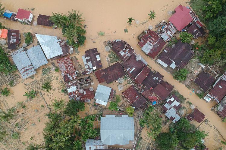 Foto udara kondisi banjir yang merendam pemukiman di Kampung Tarandam, Nagari Pasar Muara Labuah, Kab.Solok Selatan, Sumatera Barat, Jumat (13/12/2019). Data BPBD Solok Selatan menyebutkan banjir bandang mengakibatkan 1000 unit rumah terendam banjir, enam unit hanyut, satu jembatan putus dan satu orang tewas.