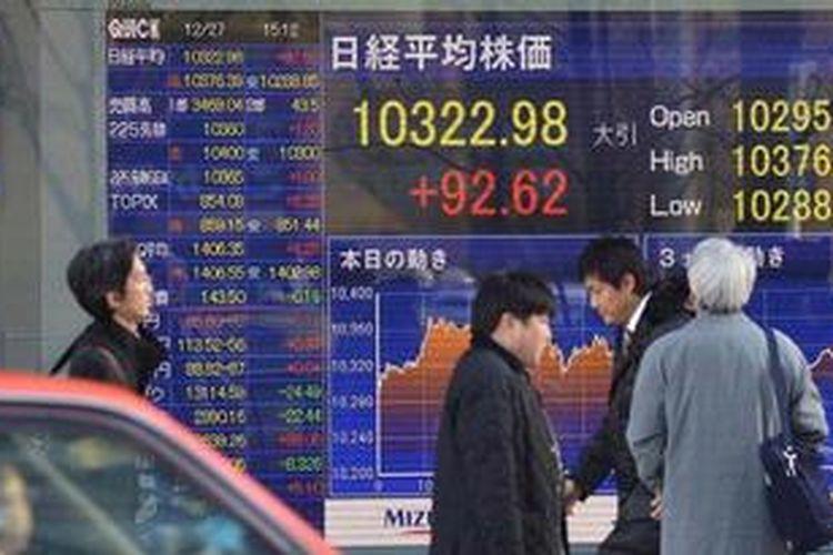 Ilustrasi : Para pejalan kaki melewati sebuah papan elektronik yang memajang perkembangan di bursa saham Jepang.