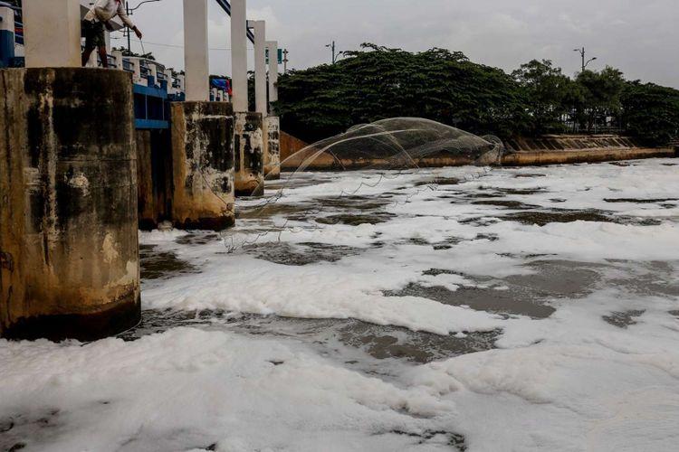 Warga menebar jala saat memancing di sungai berbusa di Perairan Kanal Banjir Timur (KBT), kawasan Marunda, Jakarta Utara, Sabtu (24/3/2018). Busa yang memenuhi KBT selepas Pintu Air Weir 3 Marunda ini akibat limbah rumah tangga.