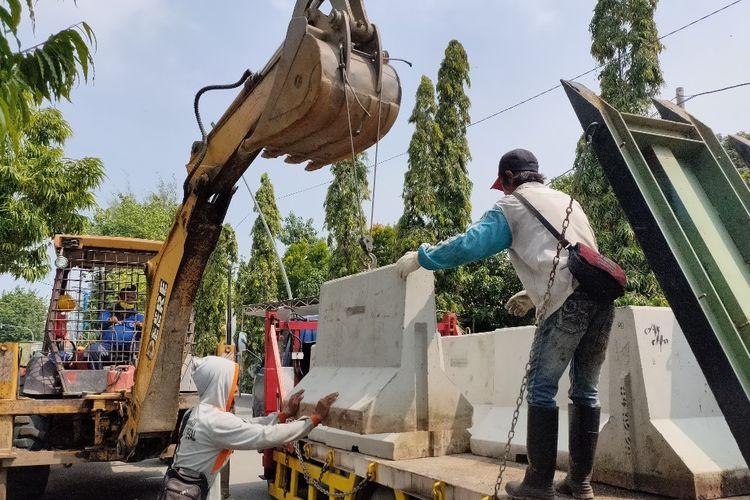 Petugas DPUPR Kota Tegal dengan bantuan alat berat mengangkut beton  pembatas jalan untuk menutup akses masuk ke perkampungan di jalan nasional dan provinsi, Rabu (22/4/2020)