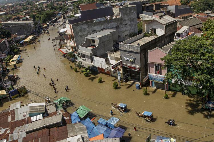 Warga menembus banjir yang melanda ruas Jalan Raya Dayeuhkolot, Kabupaten Bandung, Jawa Barat, Jumat (17/11). Sedikitnya 1.033 jiwa terdampak banjir masih mengungsi di beberapa posko BPBD Kabupaten Bandung. Sebanyak 4.097 unit rumah, 10 gedung sekolah, dan 27 tempat ibadah di tiga kecamatan terendam banjir akibat curah hujan yang tinggi dan meluapnya Sungai Citarum. ANTARA FOTO/Novrian Arbi/kye/17