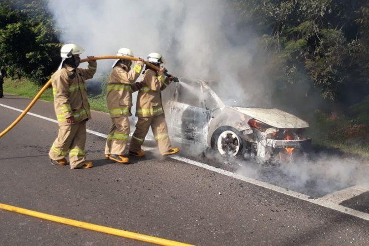 Petugas pemadam kebakaran memadamkan api yang membakar mobil sedan di KM3 Halim Tol Jakarta-Cikampek, Rabu (27/5/2020) pagi.