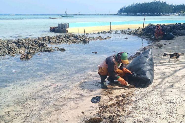 Petugas PPSU Kep Seribu mengumpulkan tumpahan minyak yang sudah berubah menjadi padat di pinggir pantai Pulau Pari, Kep. Seribu, Rabu (12/8/2020)