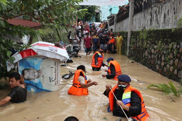 Sejumlah warga dievakuasi oleh personil Brimob Polda Sumut bersama warga lainnya di Kelurahan Sei Mati, Kecamatan Medan Maimun pada Jumat (4/12/2020). Banjir di Sungai Deli membuat ribuan rumah terendam banjir.
