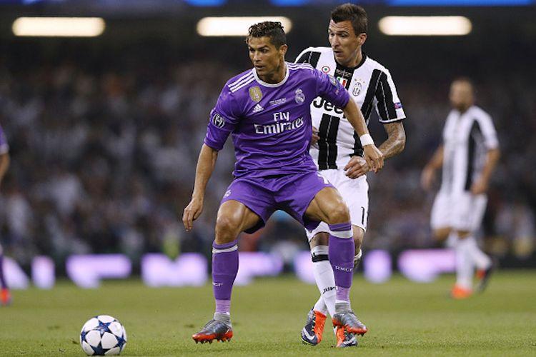 Cristiano Ronaldo mencoba melindungi bola dari sergapan Mario Mandzukic pada laga final Liga Champions antara Real Madrid dan Juventus di Stadion Millenium, Sabtu (3/6/2017).