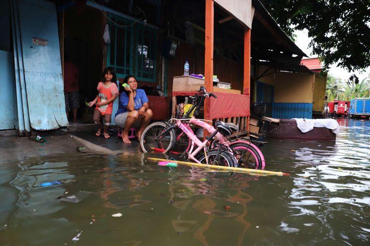 Warga tetap beraktivitas meski rumah mereka terendam banjir di wilayah Teluk Gong, Penjaringan, Jakarta Utara, Sabtu (4/1/2020).Hujan lebat di awal tahun membuat kawasan teluk gong masih terendam banjir.