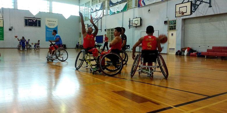 Para pemain timnas basket kursi roda Indonesia sedang melakukan pemanasan jelang laga uji coba melawan Thailand.