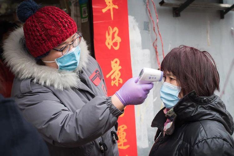 Seorang relawan komunitas mengecek suhu tubuh seorang perempuan di Paviliun Yellow Crane di Wuhan, China, pada Jumat (7/2/2020). Wabah virus corona yang mewabah di China sejak Desember 2019 dilaporkan telah membunuh 722 orang.