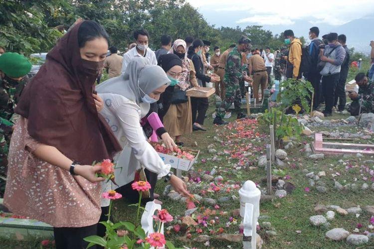 Warga melakukan tabur bunga di lokasi pemakaman massal korban bencana alam gempa bumi 2018. Senin, (28/9/2020