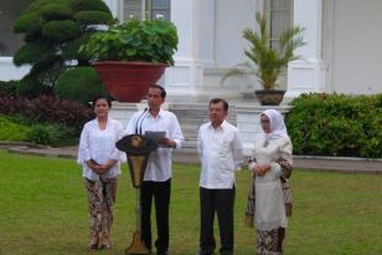 Presiden Joko Widodo dan Wakil Presiden Jusuf Kalla berserta istri masing-masing dalam pengumuman kabinet di halaman Istana Negara, Minggu (26/10/2014).