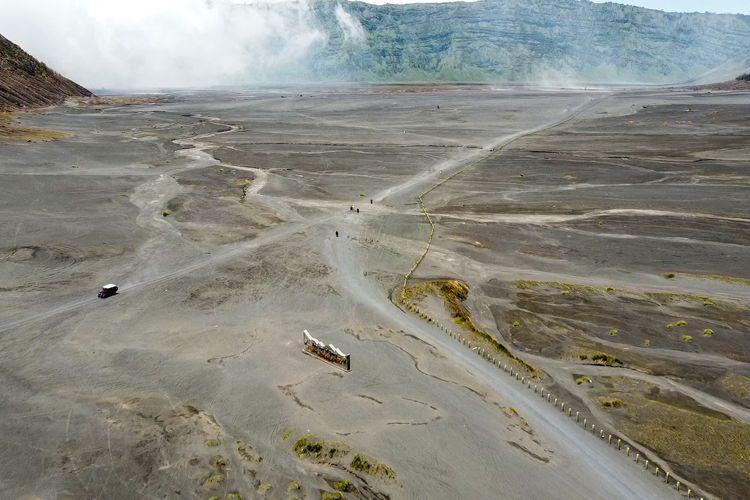 Kendaraan melintas di lautan pasir Bromo.