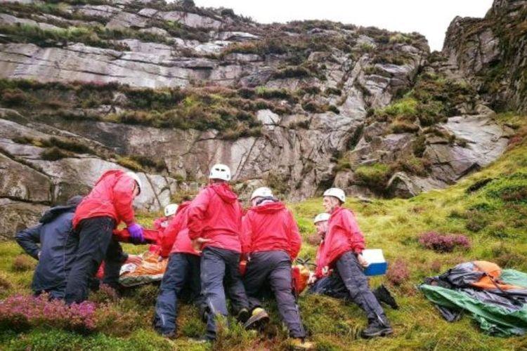 Tim penyelamat Pegunungan Mourne memeriksan kondisi remaja yang tertimpa domba saat berada di gunung di Irlandia Utara.