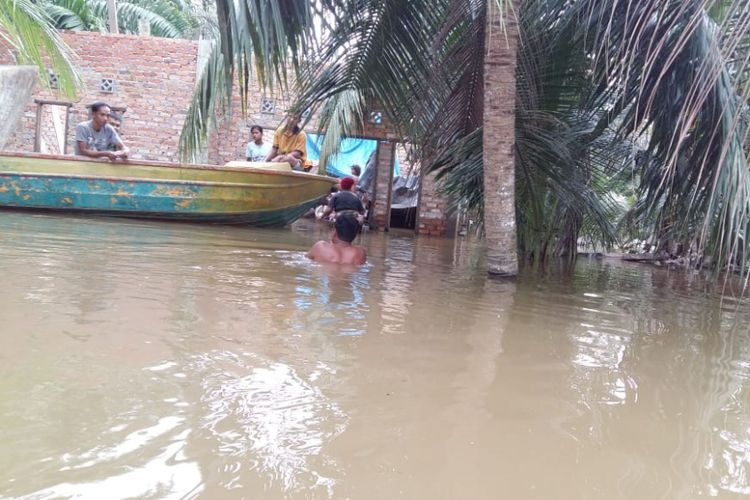 Warga masih bertahan di rumah dalam kondisi banjir di Desa Buluh Cina, Kecamatan Siak Hulu, Kabupaten Kampar, Riau, Senin (17/12/2018).