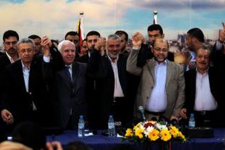 PM Hamas, Ismail Haniya (tengah) diapit delegasi PLO dari Tepi Barat, saat mengumumkan kesepakatan Hamas dan Fatah membentuk pemerintahan bersama sebelum menggelar pemilu dalam tujuh bulan.