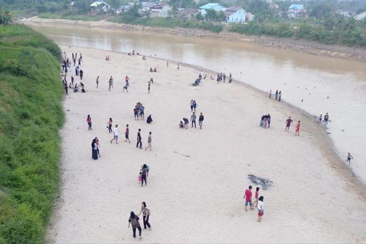 Ratusan warga tampak menyemuti Sungai Landak, di Kecamatan Ngabang, Kabupaten Landak, Kalimantan Barat, Kamis (15/8/2019).
