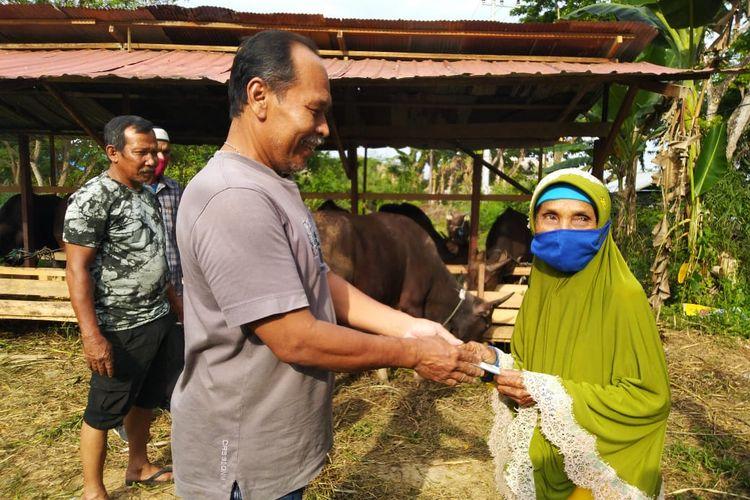 Nenek Sumiyati saat membayar sapi dan kambing yang dibeli di salah satu peternak sapi di Tenggarong, Kutai Kartanegara, Kaltim, Kamis (30/7/2020).