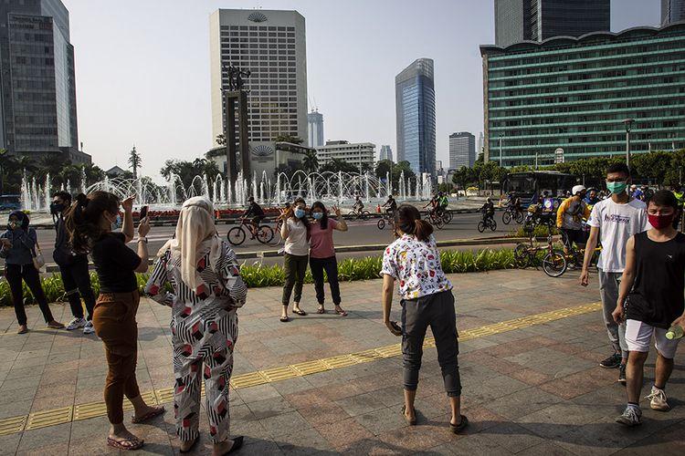 Warga beraktivitas di kawasan Bundaran Indonesia, Jakarta, Minggu (13/9/2020). Jelang penerapan Pembatasan Sosial Berskala Besar (PSBB) total yang rencananya dilaksanakan pada Senin (14/9/2020) masih banyak masyarakat yang melakukan kegiatan di luar rumah.