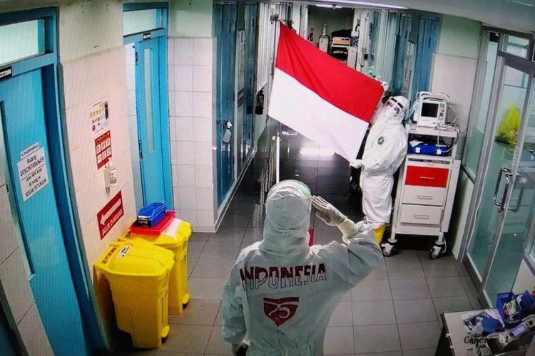 Petugas media RSUP Dr Sardjito Yogyakarta saat mengelar upacara hormat bendera Merah Putih dalam rangka HUT ke 75 RI. Kegiatan tersebut dilakukan di ruang isolasi Gatotkaca RSUP Dr Sardjito, Yogyakarta