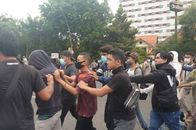 Polisi menangkap pengunjuk rasa di depan Gedung Negara Grahadi Surabaya, Selasa (20/10/2020).