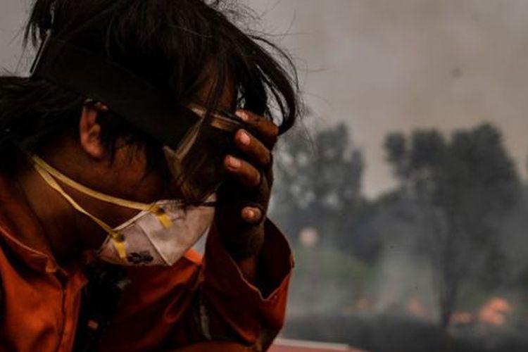 Seorang petugas pemadam kebakaran berupaya mematikan api yang melanda kawasan gambut di Pulang Pisau, Kalimantan Tengah, Jumat (13/09). Tagar #IndonesiaDaruratAsap mulai muncul pada Sabtu (14/09) dan sudah ada 16.300 cuitan menggunakan tagar ini hingga pukul 15.40 WIB