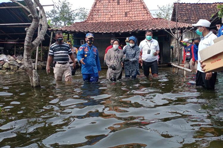 Menteri Sosial Republik Indonesia, Tri Rismaharini, menerobos genangan banjir seusai memberikan bantuan kepada korban banjir di Dukuh Dempel Desa Kalisari Kecamatan Sayung Kabupaten Demak Jawa Tengah yang sudah sepekan ini terendam banjir, Jumat (12/2/2021).