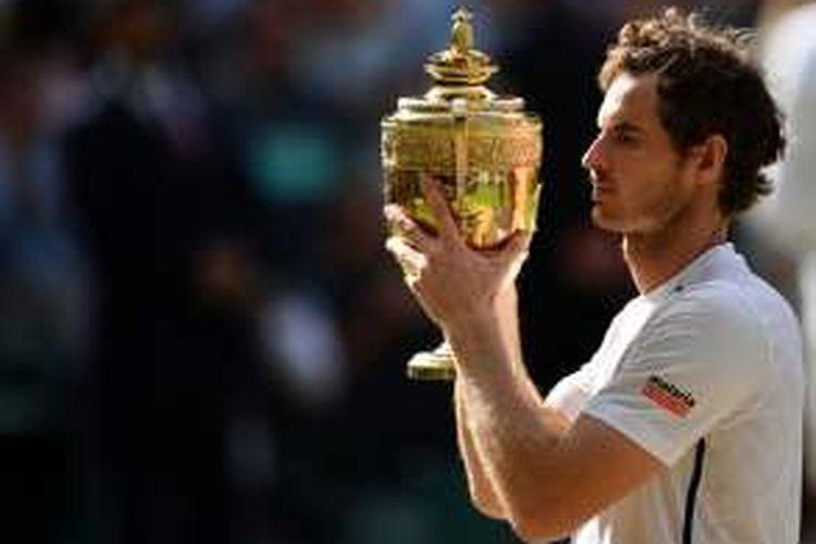 Petenis Inggris Raya, Andy Murray, memgang trofi juara Wimbledon yang didapat setelah mengalahkan petenis Kanada, Milos Raonic, pada laga final di The All England Lawn Tennis Club, Minggu (10/7/2016).