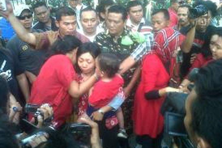 Istri Serda Ucok Tigor Simbolon, Enis Nurwati saat menemui wartawan sambil mengendong anaknya yang masih balita.