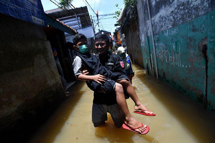 Seorang warga membawa anaknya yang baru selesai dikhitan melewati banjir di kawasan permukiman di Petogogan, Kebayoran Baru, Jakarta Selatan, Senin (5/10/2020). Banjir tersebut terjadi akibat meluapnya Kali Krukut.