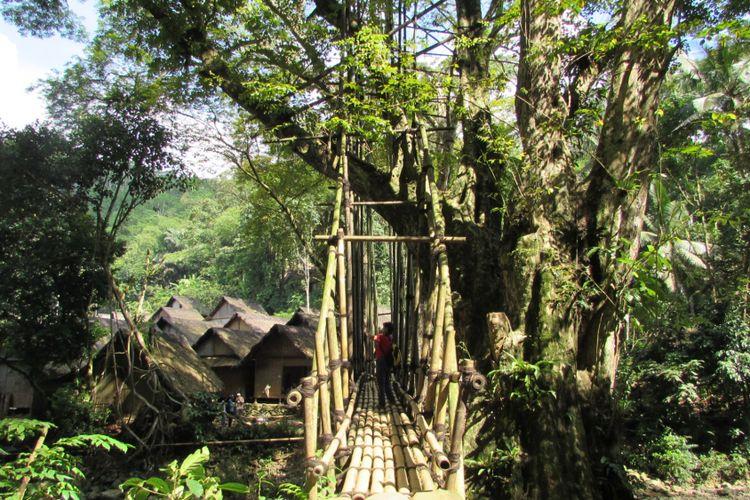 Seorang wisatawan berfoto di atas jembatan yang dibangun dari bilah-bilah bambu.