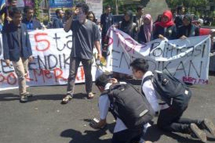 Demo Hardiknas oleh Mahasiswa UB Malang, Jawa Timur, Jumat (2/5/2014). Mahasiswa mempraktikkan pungli yang dilakukan oleh