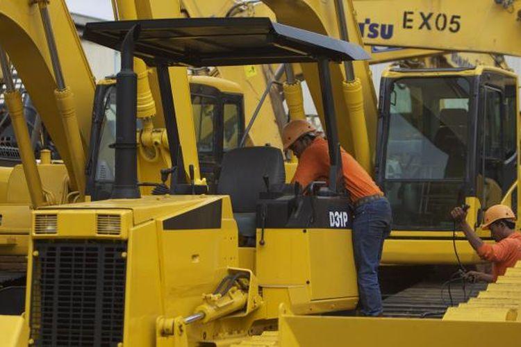 Ilustrasi: Pekerja mengecek alat berat di PT United Tractors Tbk
