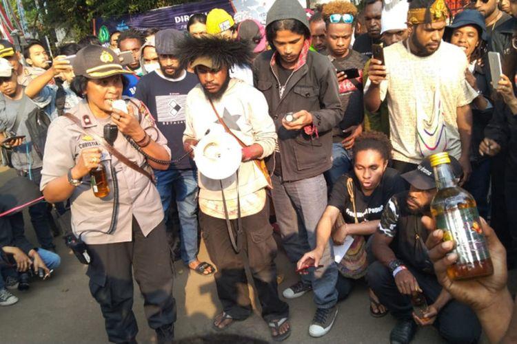 Para mahasiswa asal Papua saat menyerahkan kiriman minuman keras dari oknum polisi dalam aksi solidaritas di Gedung Sate, Jalan Diponegoro, Kamis (22/8/2019).
