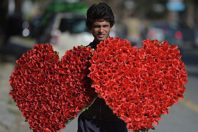 Seorang pedagang membawa buket bunga berbentuk hati yang dijual menjelang perayaan hari Valentine di jalanan kota Islamabad, Pakistan. Pemerintah Pakistan telah melarang perayaan hari kasih sayang tersebut sejak 2017 lalu.