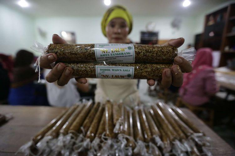 Pekerja membungkus dodol untuk dipasarkan di rumah produksi dodol nyonya Lauw di kawasan Tangerang, Banten, Senin (28/1/2019). Menjelang Imlek permintaan dodol betawi mengalami peningkatan tiga kali lipat dengan harga jual Rp53.000 per kilogramnya.