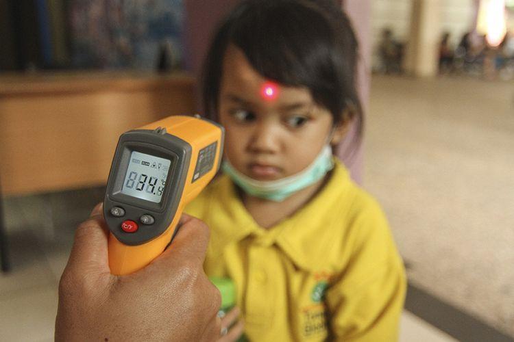 Petugas sekolah memeriksa suhu tubuh siswa menggunakan termometer non kontak saat sosialisasi di Sekolah Tunas Global, Depok, Jawa Barat, Selasa (3/3/2020). Kegiatan tersebut sebagai upaya antisipasi Virus Corona pada usia dini dengan mengukur suhu tubuh saat memasuki sekolah dan mensosialisasi penggunaan masker yang benar saat sakit.