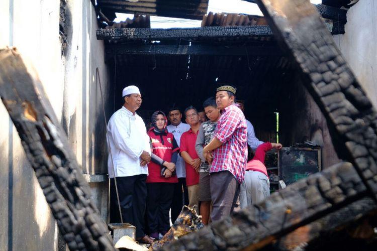 Mulyono (kemeja kotak-kotak) dan Wali Kota Magelang Sigit Widyonindito saat melihat kondisi rumah pasca musibah kebakaran, Jumat (13/4/2018). Musibah terjadi pada Kamis (12/4/2018), mengakibatkan istri Mulyono meninggal dunia.
