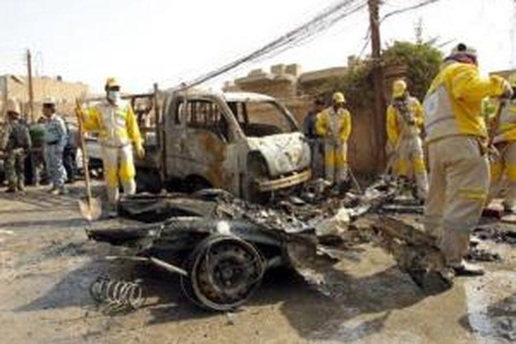 Para pekerja membersihkan sisa-sisa serangan bom mobil di pusat kota Baghdad, Irak, Rabu (5/3/2014).