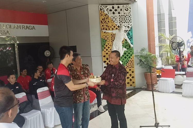 Menpora Imam Nahrawi (kanan) saat memberikan kue ulang tahun kepada pebulu tangkis Indonesia, Hendra Setiawan dalam acara pemberian bonus untuk para pebulu tangkis yang sudah menorehkan medali di Kejuaraan Dunia 2019, baik badminton maupun para badminton, di Kantor Kemenpora, Jakarta, Rabu (28/8/2019).