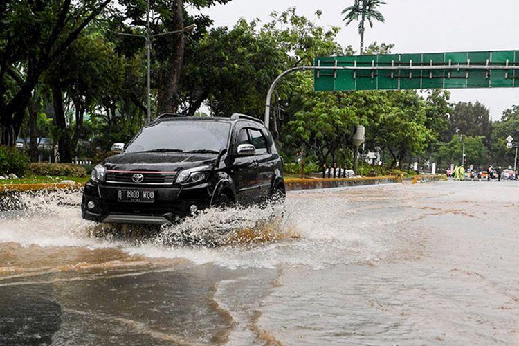 Pengendara mobil melintasi genangan di Jalan Medan Merdeka Barat, Jakarta, Minggu (2/2/2020). Hujan deras yang mengguyur Jakarta pada Minggu (2/2) pagi menyebabkan beberapa ruas jalan di ibu kota tergenang banjir dengan ketinggian 10-50 centimeter.