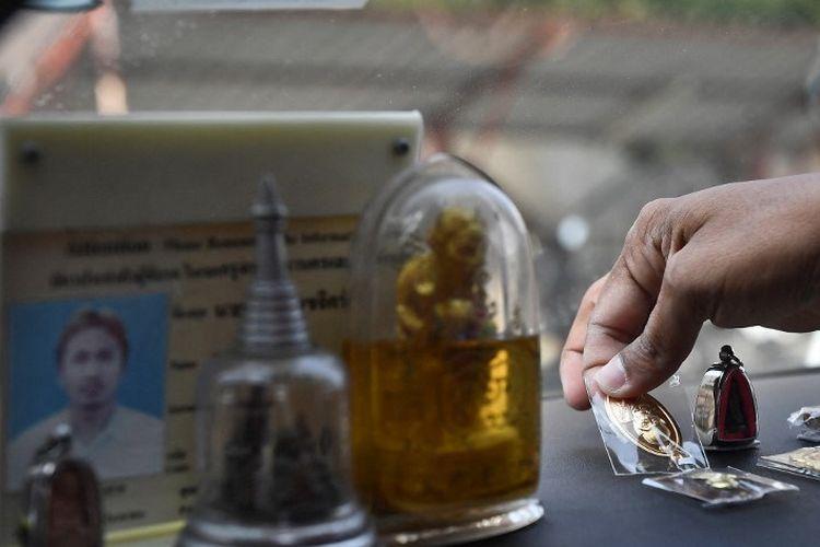 Sopir taksi Wasan Sukjit meletakkan beberapa amulet pelindung Buddha di dasbor mobilnya sebelum berangkat bekerja di Bangkok.