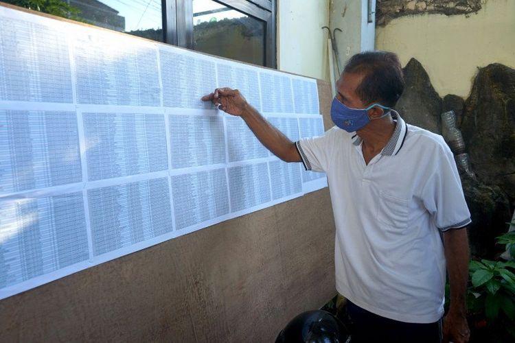 Seorang warga melihat daftar penerima bantuan sosial untuk warga terdampak COVID-19 di kantor kelurahan, Kota Surabaya, Jawa Timur, Kamis (7/5/2020). ANTARA/HO-Humas Pemkot Surabaya