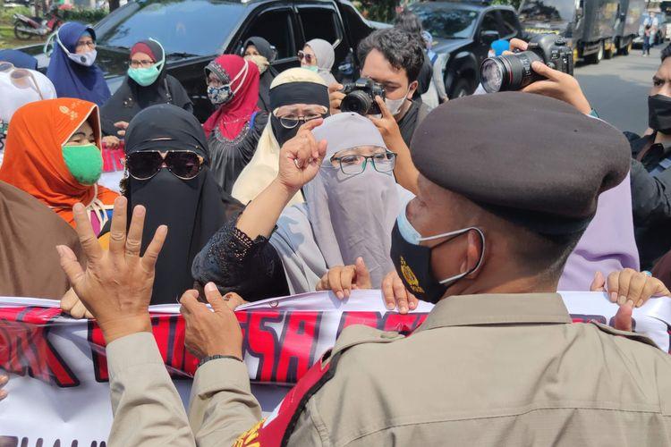 Polisi melarang massa Rizieq Shihab untuk berorasi dan membentangkan spanduk di Pengadilan Negeri Jakarta Timur, Jumat (19/3/2021). Massa ibu-ibu yang berjumlah sekitar 20 orang itu pun akhirnya diusir mundur sampai ke belakang gedung pengadilan.