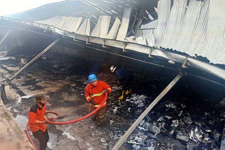 Petugas memadamkan api yang membakar gudang milik PT Hartono Istana Teknologi yang terletak di Kecamatan Sayung , Kabupaten Demak  Jateng