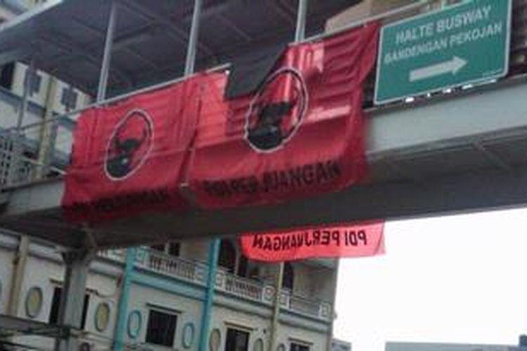 Atribut sebuah partai politik yang dipasang di halte busway Bandengan Pekojan yang menjadi tempat pengungsian penduduk, Selasa (22/1/2013)