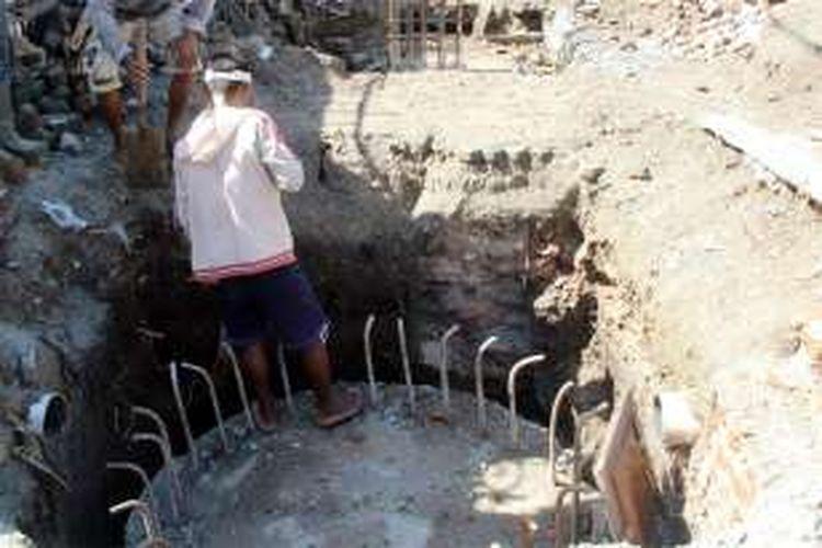Seorang pekerja menunjukkan sumuran yang di dalamnya terdapat batu kali pada kedalaman 1 meter. Pondasi ini diduga berasal dari masa pemerintahan kolonial Belanda aau masa VOC
